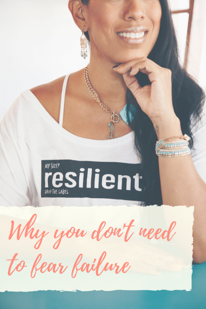 "A smiling woman wears a t-shirt that reads ""resilient."" Pink words say ""Why you don't need to fear failure"" over the top of the picture."